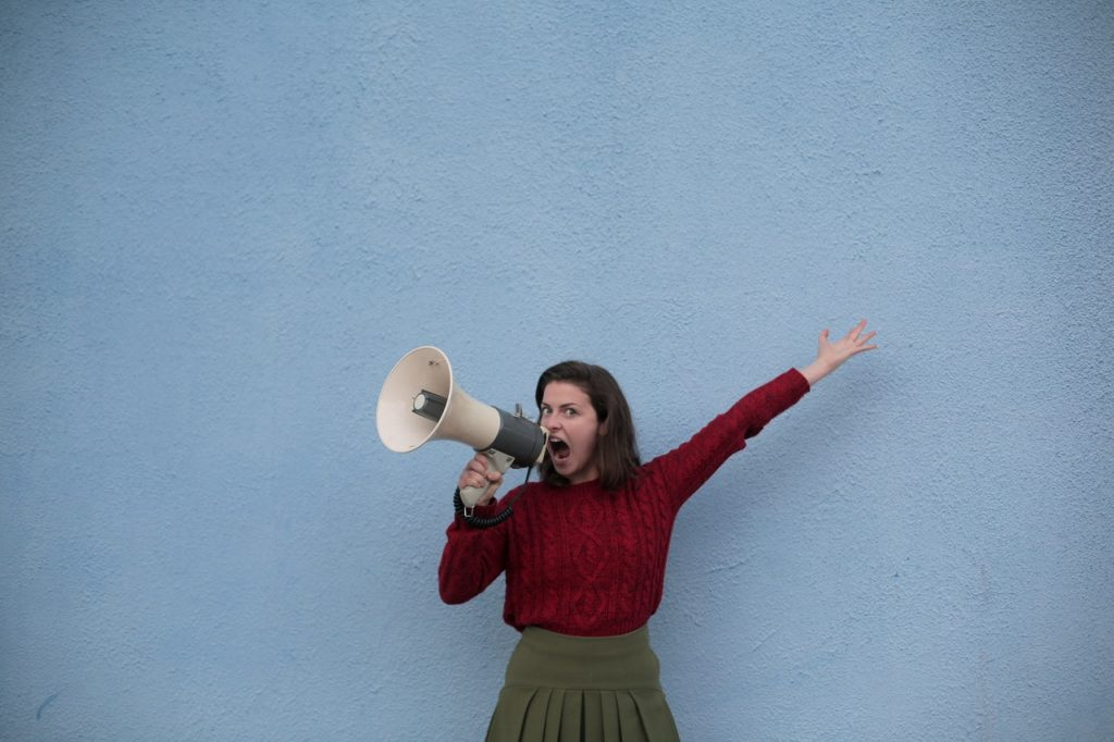 a girl shouts using a horn