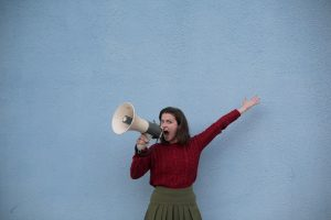 a girl shouts using a horn